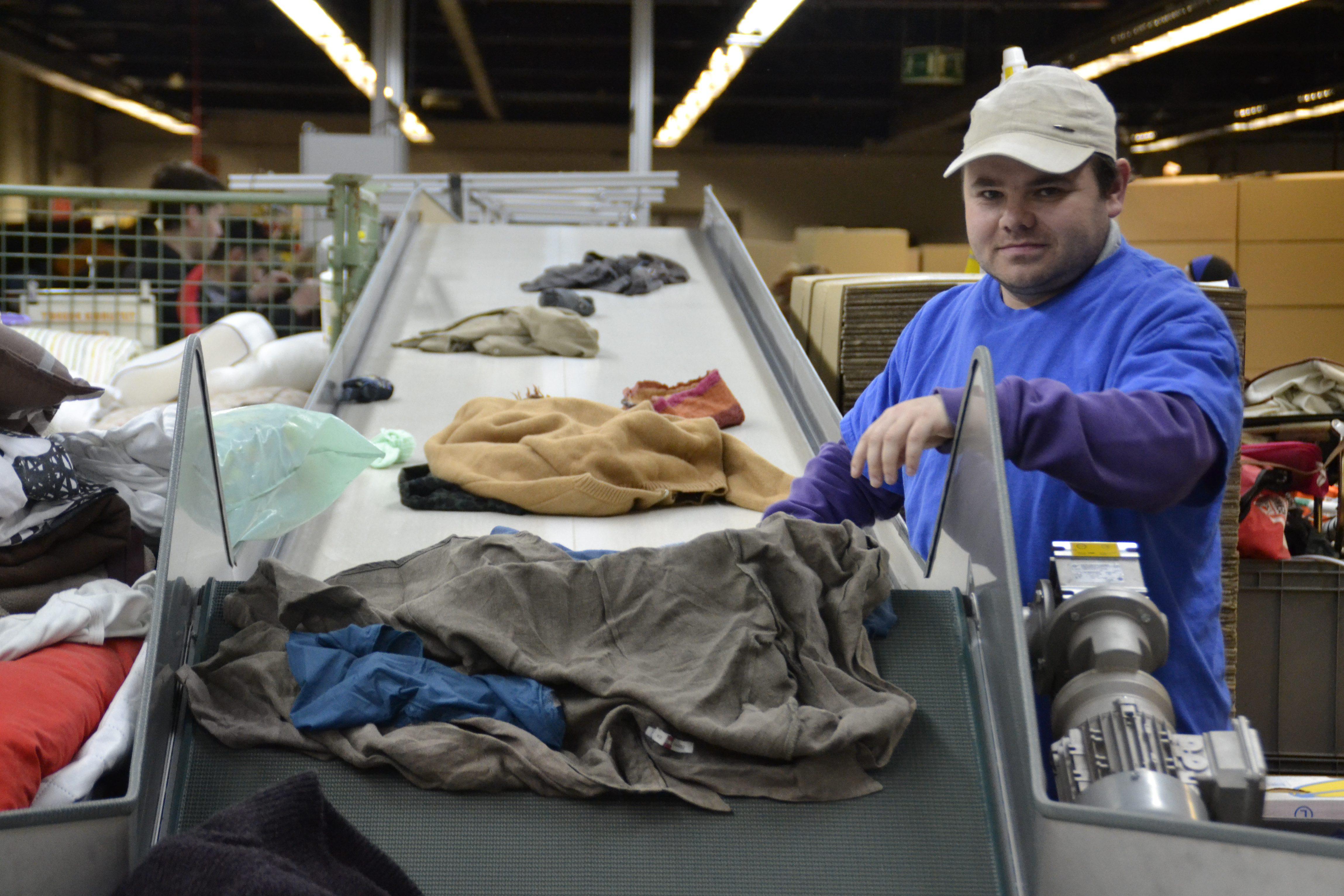 Kevin Cuylaerts aan het werk aan de sorteerlijn van De Kringwinkel Zuiderkempen
